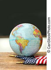 Globo y bandera en el escritorio de la escuela