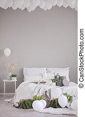 Globos blancos bajo el techo del elegante dormitorio gris con cama cómoda con ropa de cama blanca y acentos grises, foto real con espacio de copia en la pared vacía