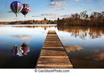 Globos de aire caliente sobre el lago del atardecer con jetty