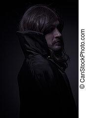 Goth, hombre de pelo largo y abrigo negro