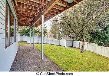 Gran patio trasero con hierba.