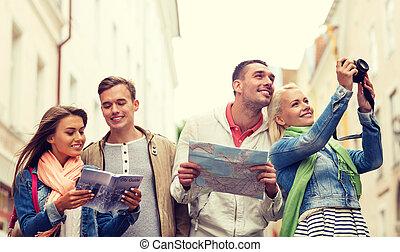 Grupo de amigos con guía de la ciudad, mapa y cámara