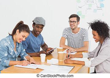 Grupo de artistas felices en discusión en el escritorio