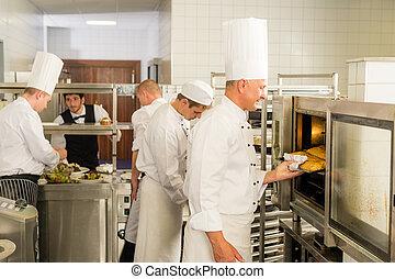 Grupo de cocineros en la cocina profesional