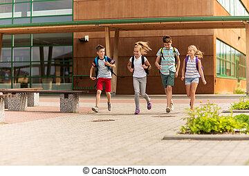 Grupo de estudiantes felices de primaria corriendo
