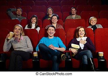 Grupo de personas sonrientes viendo películas en el cine