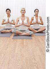 Grupo interracial de tres hermosas mujeres en posición de yoga