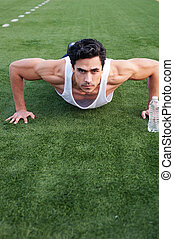 Guapo, joven atleta latino haciendo flexiones
