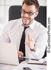 Haciendo tu negocio más fácil. Un joven apuesto con camisa y corbata apuntándote y sonriendo mientras se sienta en su lugar de trabajo
