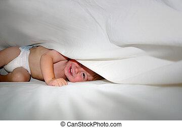 Happy Baby jugando bajo sábanas en la cama