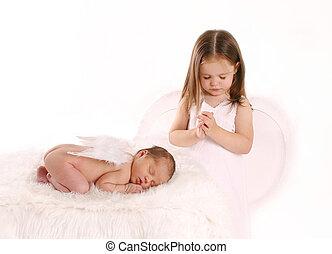 Hermana rezando por el ángel recién nacido