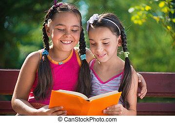 Hermanas leyendo libros en el parque de verano