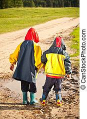 Hermanos caminando en charcos