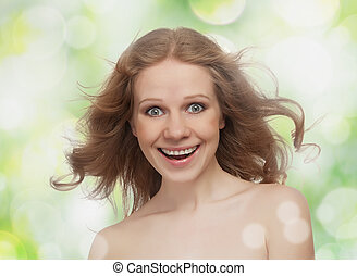 Hermosa chica alegre con el pelo suelto ríe en el fondo verde de la primavera y el verano al aire libre