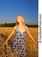Hermosa chica en el campo de trigo a la hora del atardecer