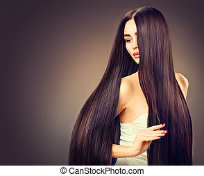 Hermosa chica modelo morena con el pelo largo y negro sobre el fondo oscuro