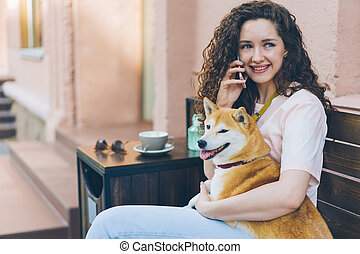 Hermosa dama hablando por teléfono móvil abrazando shiba inu perro al aire libre en el café