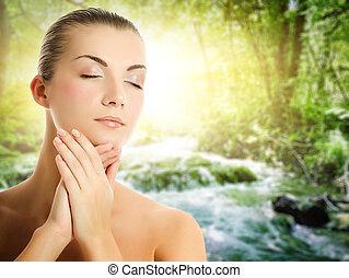 Hermosa joven aplicando cosméticos orgánicos a su piel