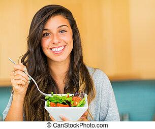 Hermosa joven comiendo un plato de ensalada orgánica saludable