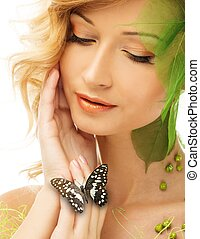 Hermosa joven con un traje de primavera conceptual con mariposa en la mano