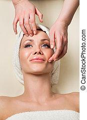 Hermosa joven recibiendo masaje facial.
