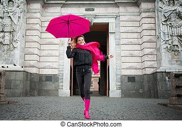 Hermosa joven y feliz mujer rubia con un colorido paraguas en la calle. El concepto de positividad y optimismo
