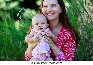 Hermosa madre feliz sosteniendo a la niña con amor