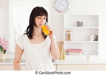 Hermosa morena bebiendo un vaso de jugo de naranja