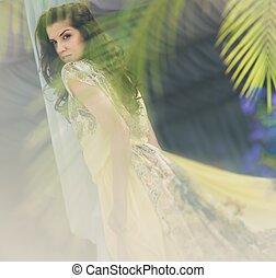 Hermosa morena con cabello largo y vestido amarillo