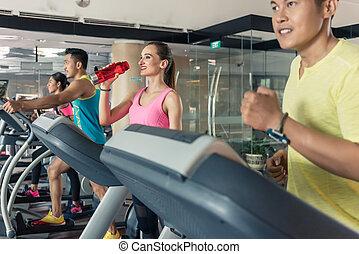 Hermosa mujer bebiendo agua durante el entrenamiento en un club de fitness de moda