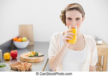 Hermosa mujer bebiendo un vaso de jugo de naranja en su cocina mirando la cámara