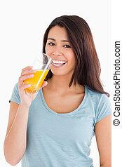 Hermosa mujer bebiendo un vaso de jugo de naranja