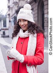 Hermosa mujer con abrigo rojo y gorra de lana y guantes con smartphone en las manos pasando por la ciudad