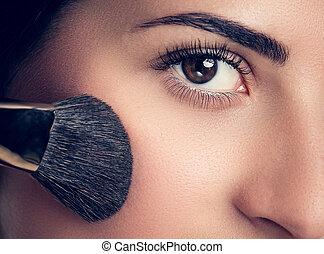 Hermosa mujer con cepillo de maquillaje