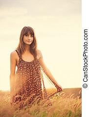 Hermosa mujer en el campo dorado al atardecer
