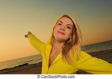 Hermosa mujer en una playa al atardecer