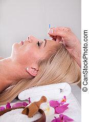 Hermosa mujer en una terapia de acupuntura en un centro de spa