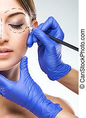 Hermosa mujer mitad cirugía plástica de cara, manos de cirujano plástico