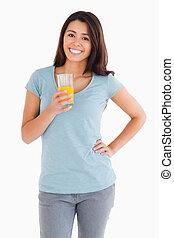 Hermosa mujer sosteniendo un vaso de jugo de naranja