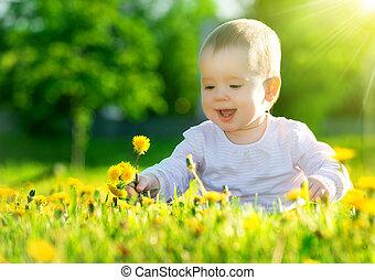 Hermosa niña feliz sentada en un prado verde con flores amarillas dientes de león en la naturaleza del parque