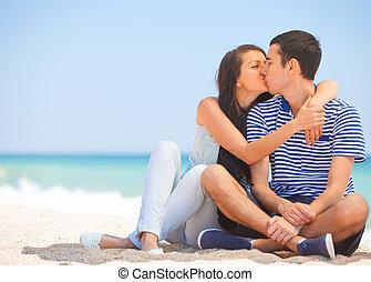 Hermosa pareja besándose en la playa.