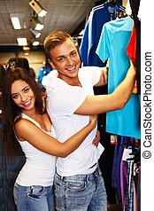Hermosa pareja joven eligiendo ropa deportiva en la salida deportiva