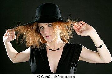 Hermosa pelirroja de negro, sombrero y joyas