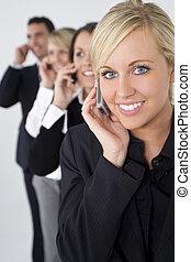 Hermosa rubia en el celular con un equipo detrás de ella