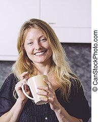 Hermosa rubia tomando café en su cocina