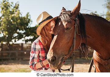 Hermosa vaquera parada y besando a su caballo