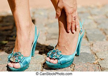 Hermosas piernas con zapatos de tacón azul y manos tocando el tobillo del dolor