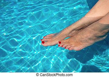 Hermosas piernas de mujer en agua azul. Hermosos y sexys pies femeninos relajándose en la piscina. Antecedentes de verano para viajar.