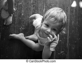 Hermoso bebé sentado en verano en la cabaña en el suelo de madera