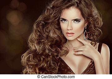 Hermoso cabello castaño, retrato de mujer de moda. Chica Modelo de Belleza con pelo largo ondulado y lujoso, aislada en el fondo oscuro